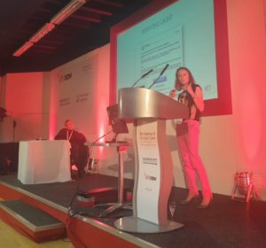 Jenny Guyat of Vet Harmony on stage speaking at the At Vets Now event November 2019